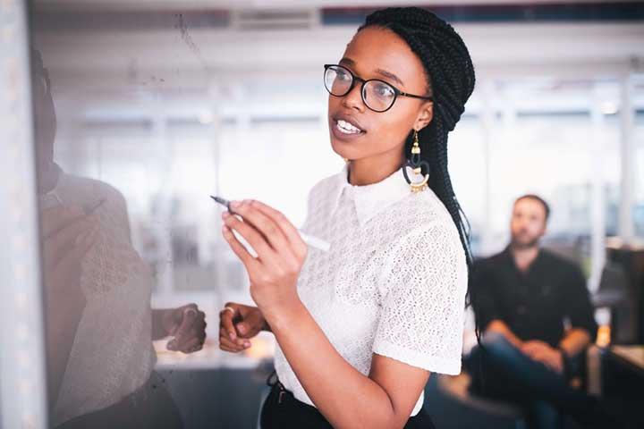 Mulher negra demonstrando um brainstorm. Imagem utilizada para contextualizar a pesquisa que 69% das mulheres ocupam cargos de liderança em empresas.